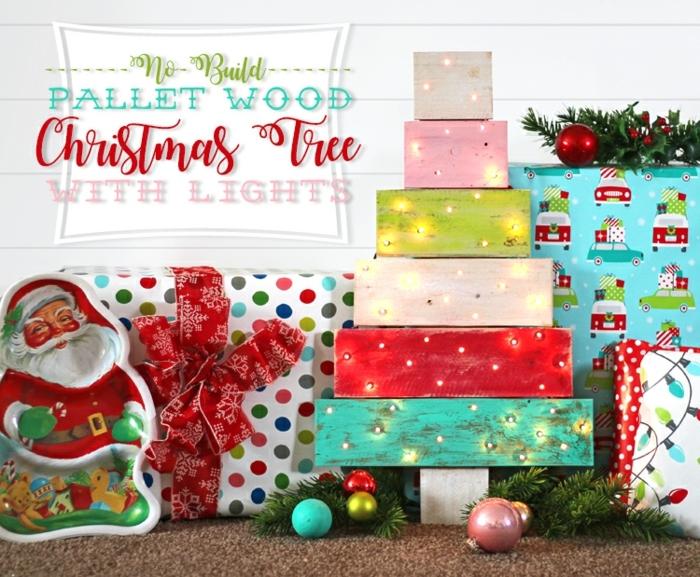 père noel en papier, grand paquet-cadeau, boules de noel, petites lumières de noel, planches de palette peintes et lampes accrochées
