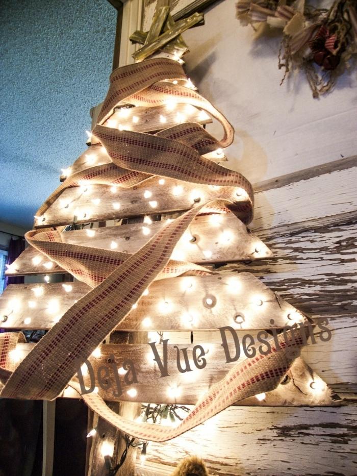 sapin lumineux en planches de bois, ruban de jute enrobé autour de l'arbre, étoile faite avec petits morceaux de bois