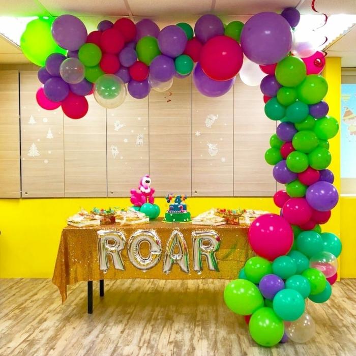 ballons en latex colorés formant une grande arche, table avec des gourmandises, sol en planches claires,