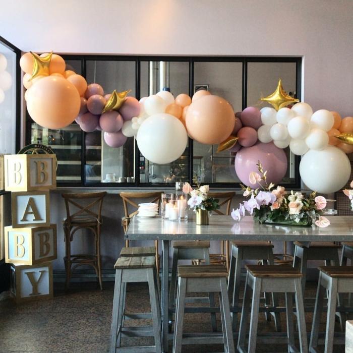 suspension de ballons mauves, oranges et blancs, longue table grise, tabourets gris et bois, chaises de bar vintage