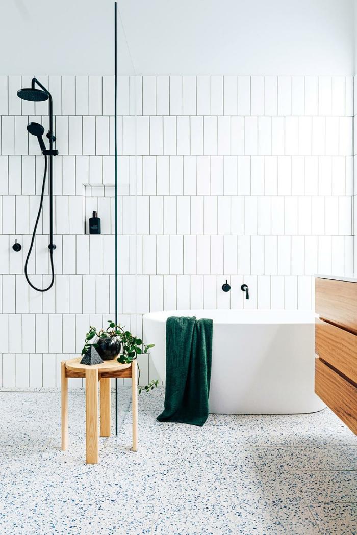 petite salle de bain blanche et bois, tabouret en bois, douche noire, serviette verte, meuble sous vasque en bois