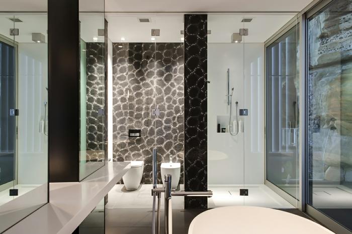 mur en pierres dans une salle de bain moderne, plan vasque blanc, sol carreaux gris, receveur de douche extra plat