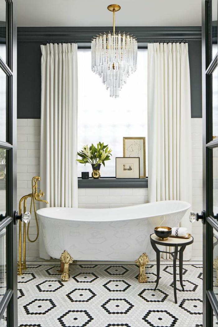 salle de bain en noir et blanc, grand plafonnier en cristal, tabouret tripode, robinet doré, rideaux lourds blancs, éléments de métal doré