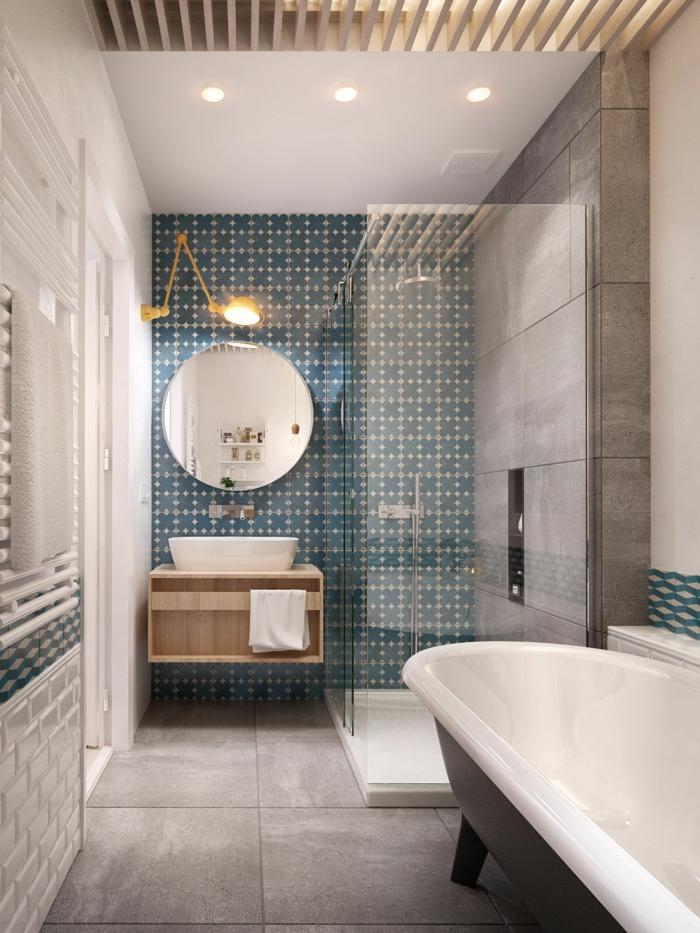 salle de bain en bleu et blanc, miroir rond, lampe murale jaune, meuble sous vasque bois, carrelage en vert et blanc et carreaux imitation béton