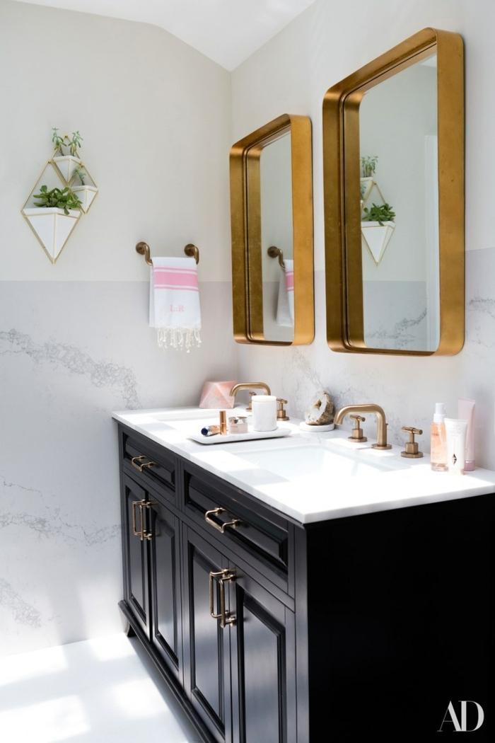 salle de bain noire et blanche, meuble sous vasque en bois foncé, deux miroirs encadrés de métal, robinets métal doré