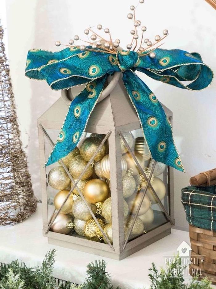 lanterne grise remplie de boules de noel couleur or et argent, ruban bleu décoratif, décoration de noel élégante luxe