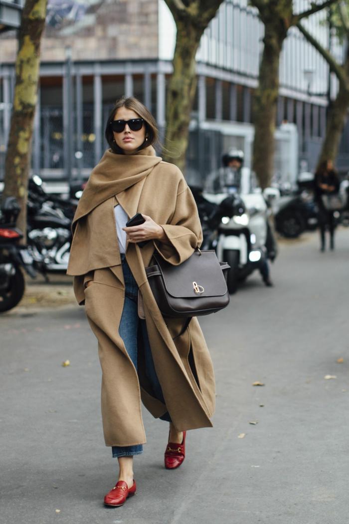 manteau long couleur clair, manches surdimensionnées, porté avec des plates rouges, jeans bleus, sac marron, lunettes de soleil