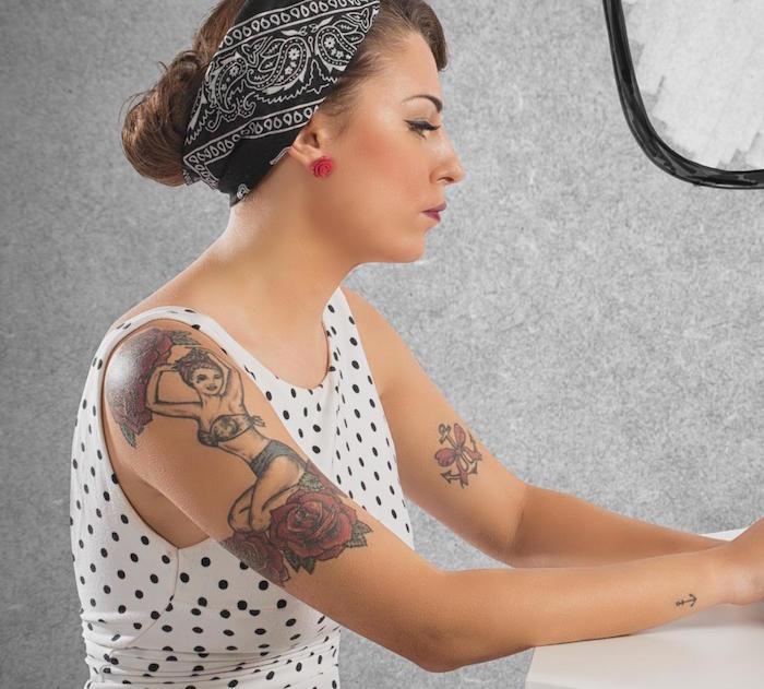 tatouage bras pour femme avec look pin up année 50 avec robe à pois et bandana noir dans les cheveux et tattoo ancre noeud sur manche