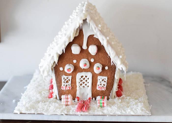 glaçage blanc pour imiter la neige sur une maisonnette aux murs et toiture en pain d épices, dessert de noel gourmand
