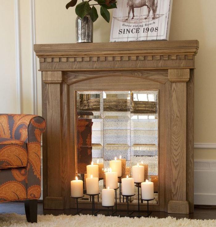 meuble en bois imitation cheminée avec faux insert miroir et bougies pour déco murale salon avec moquette et canapé orange marron