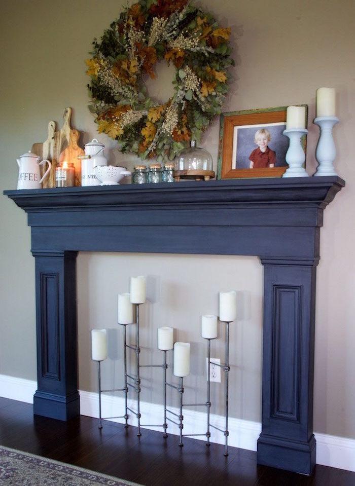 meuble en bois manteau de cheminée noir en bois avec support bougies design contre mur fris taupe et couronne végétale murale
