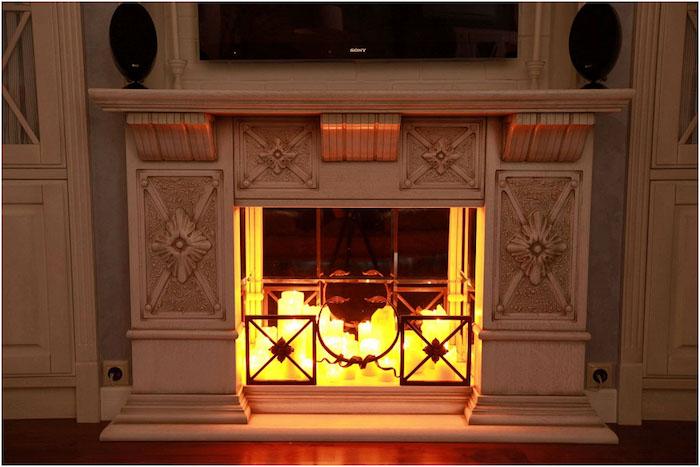 meuble imitation cheminée déco sculpté avec lot de bougies deco dans insert style faux feu avec tv murale