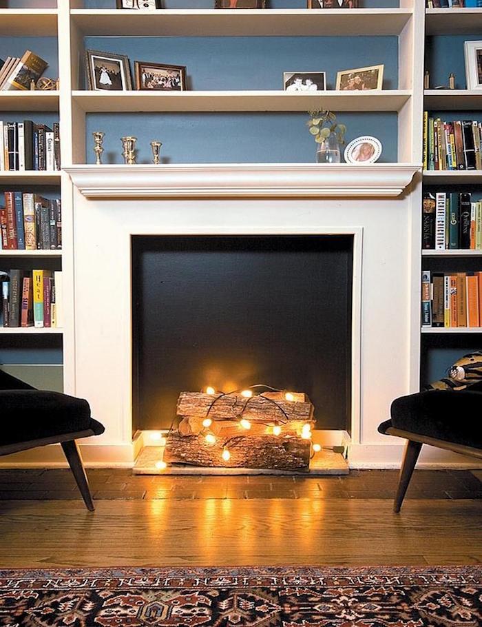 meuble déco fausse cheminée avec insert fond noir et buches décoratives avec guirlande lumineuse et grande etageres bibliotheque sur mur bleu et sol parquet