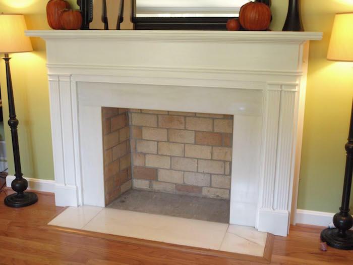 ancienne cheminée simple décorative avec manteau cadre bland et fond briques dans salon mur jaune et sol parquet