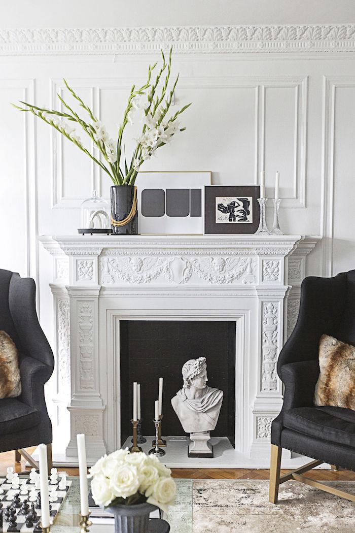 cheminée fausse avec manteau sculpté style classique dans salon blanc luxe design avec statuette buste antique et bougies dans insert à fond noir et cadre avec sol en carrelage marbre