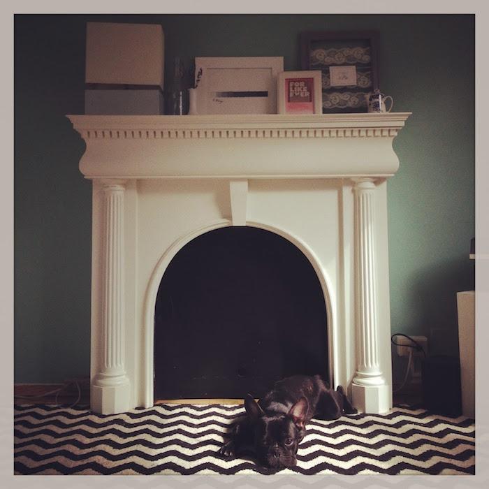 manteau de cheminée blanc taillée déco style grece antique avec fond insert noir contre mur vert et sol tapis rayé noir blanc avec petit chien