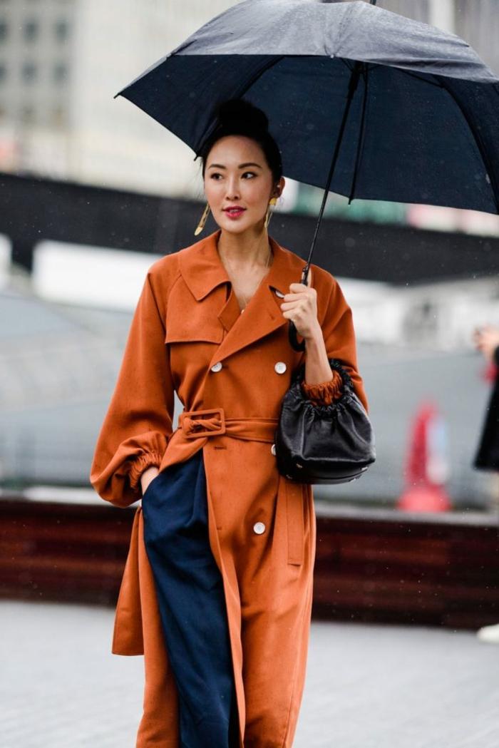 pantalon bleu, coupe ample, pardessus terracotta, sac noir cuir, grand parapluie noir, manteau long boutons