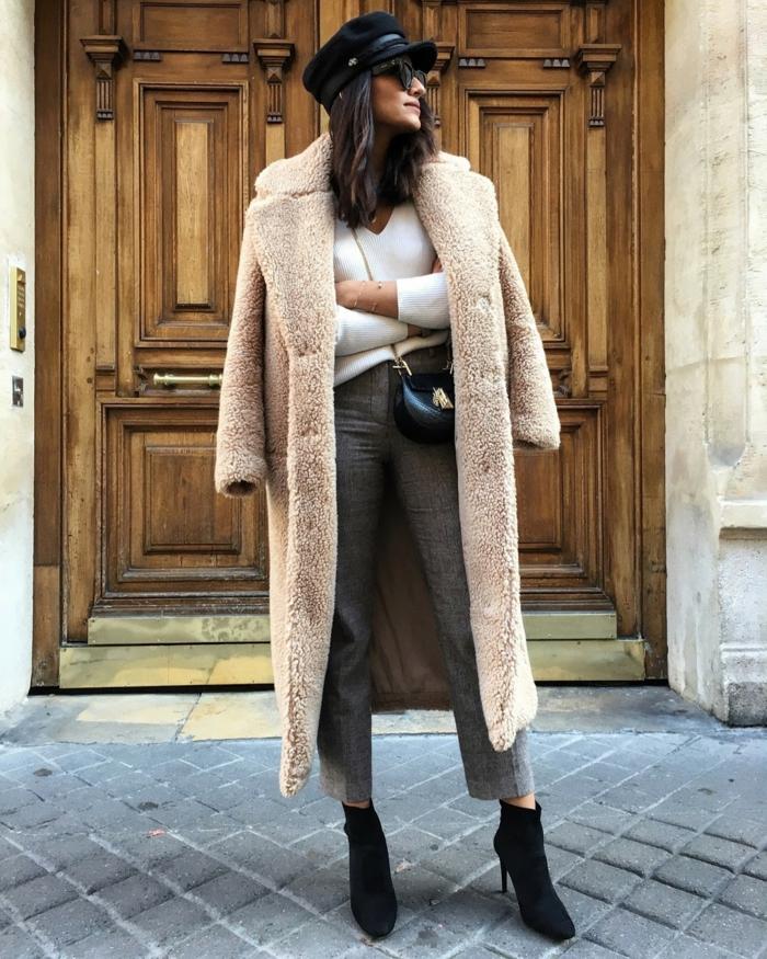 manteau teddy femme, pantalon d'hiver classique, casquette noire, pull femme hiver blanc, sac noir, grande porte en bois