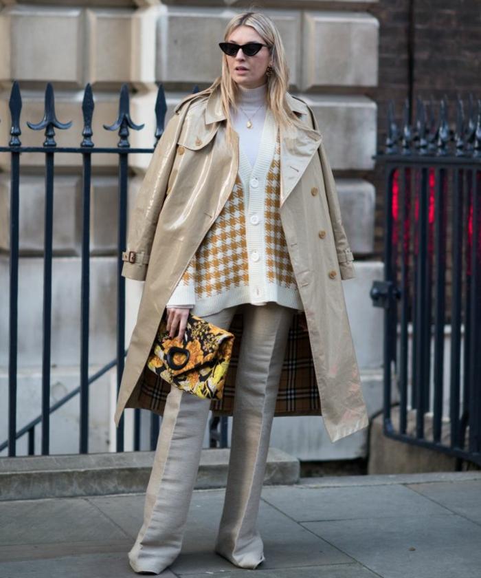 femme avec tenue élégante, sac enveloppe, pull blanc et gilet à carreaux, pantalon gris