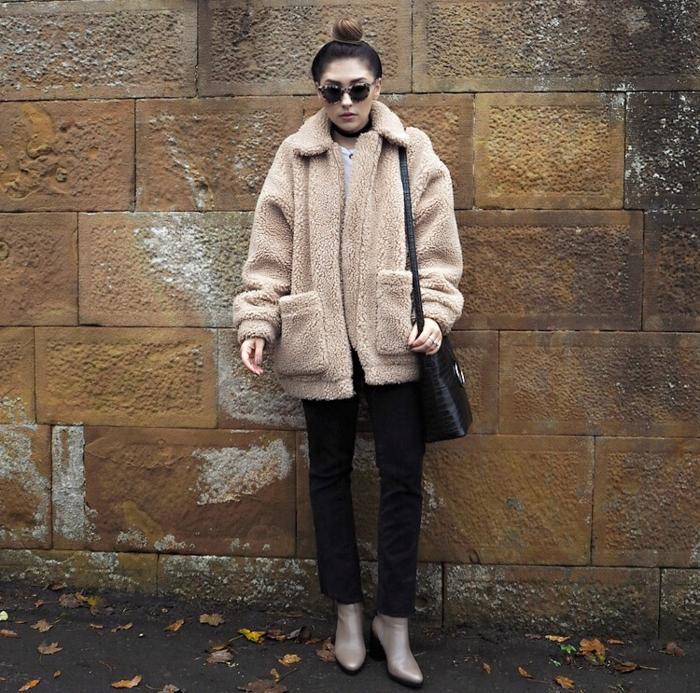 bottines couleur nude, jeans noirs, manteau teddy, chignon haut, grand sac noir porté épaule