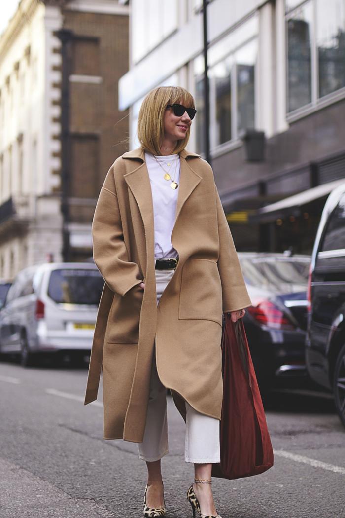 long manteau beige, pantalon blanc, tee-shirt blanc, lunettes de soleil, ceinture noire, grand sac cabas