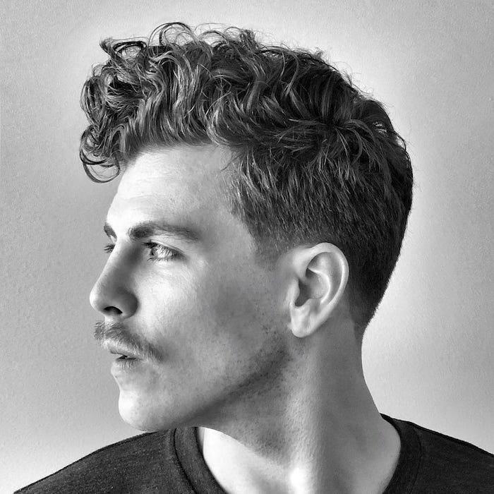 coiffure homme avec cheveux ondulés mode avec cote en dégradé et dessus plus long sur le devant et moustache hipster