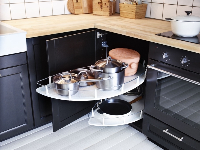 un meuble d'angle cuisine bas avec deux plateaux en mélaminé qui sortent pour accéder facilement à la vaisselle de cuisine, des placards de cuisine bas en bois et noir, contrastant avec les murs et le sol blancs