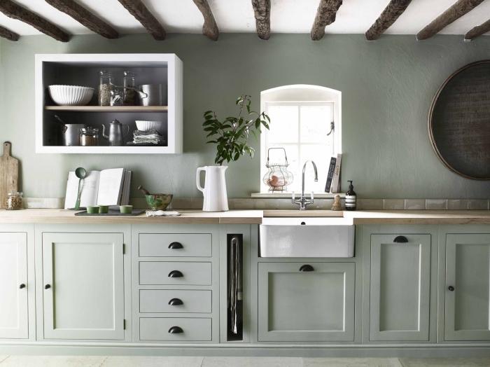 aménagement cuisine rustique avec plafond poutres bois et armoires en vert pastel, cuisine grise verdâtre de style traditionnelle