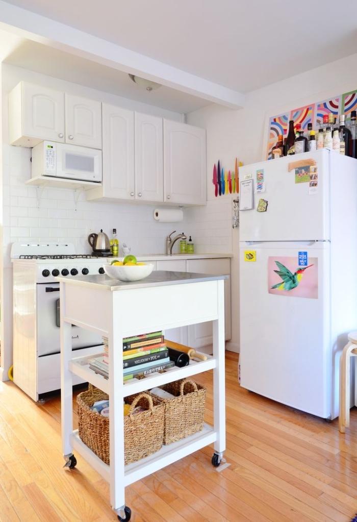 une petite cuisine blanche équipée d'un îlot central mobile à roulettes avec deux tablettes de rangement, solutions ingénieuses pour optimiser et aménager une petite cuisine