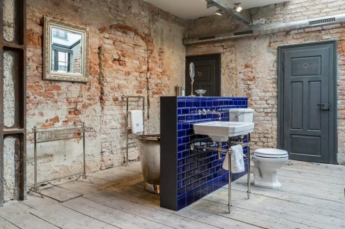 salle de bain au design brut, murs en briques, cloison bleue aux carreaux luisants, porte-serviette industriel, éclairage industriel