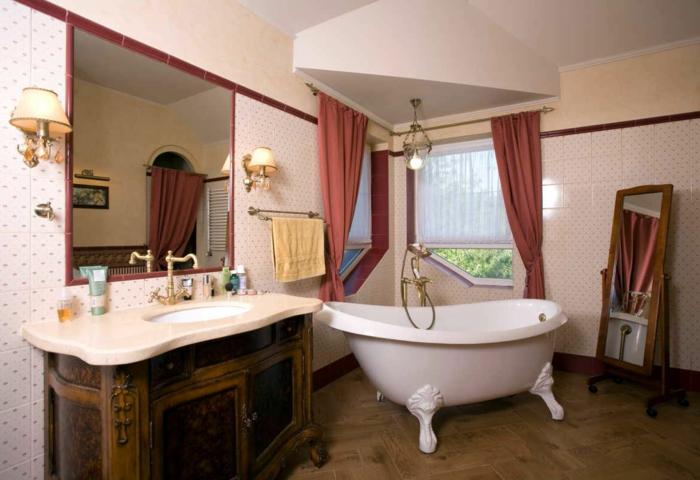 miroir sur pieds en bois, baignoire blanche, lavabo bois et blanc, rideaux rouges, papier peint blanc, sol parquet