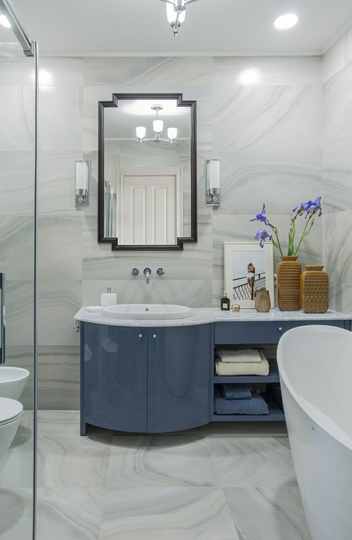 baignoire ovale vintage, sol marbré, vases marron avec fleurs bleues, grand miroir encadré, meuble sous lavabo bleu