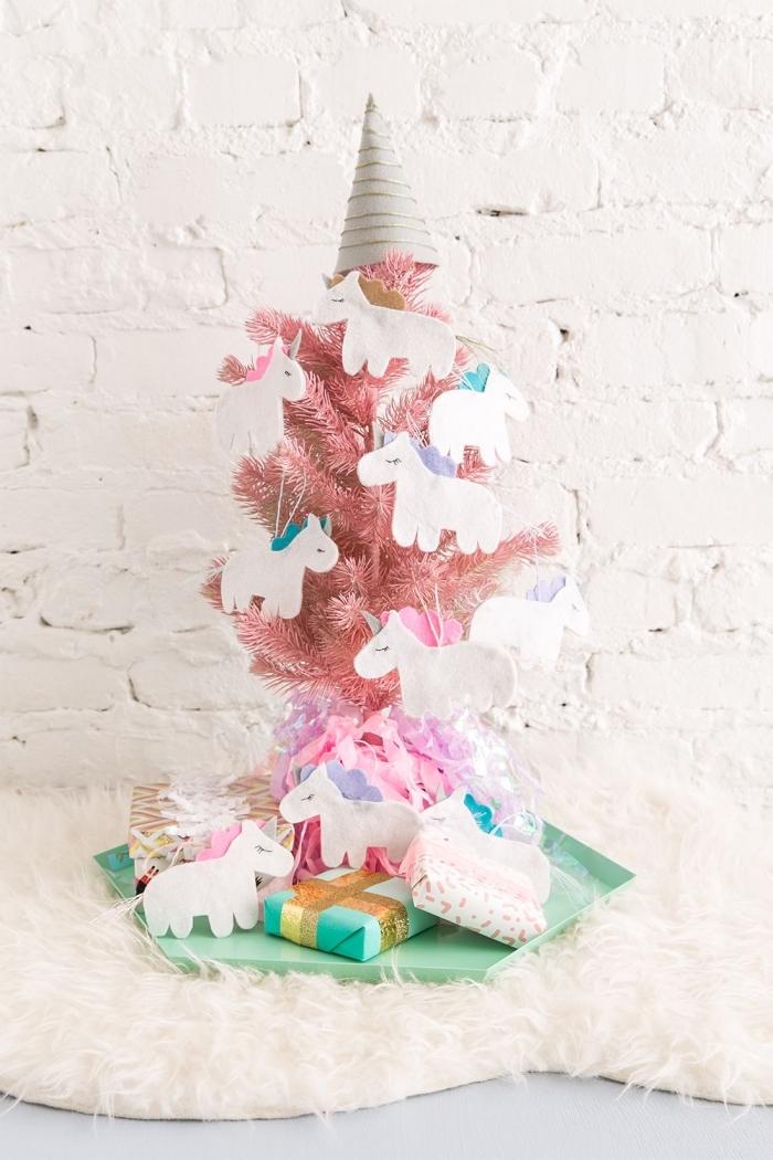 decoration de sapin de noel insolite, petit sapin artificiel rose posé sur un plateau vert menthe à l'eau, orné de suspensions licorne en papier