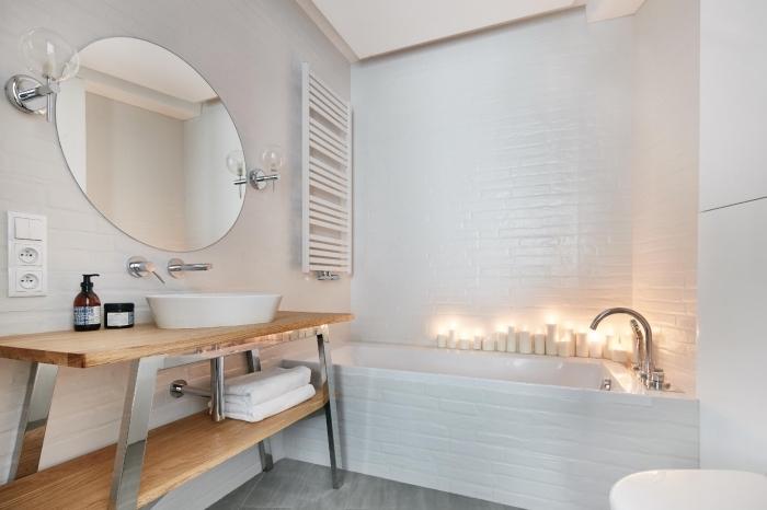 comment décorer une pièce monotone avec meuble bois et bougies, modèle de miroir rond pour salle de bain