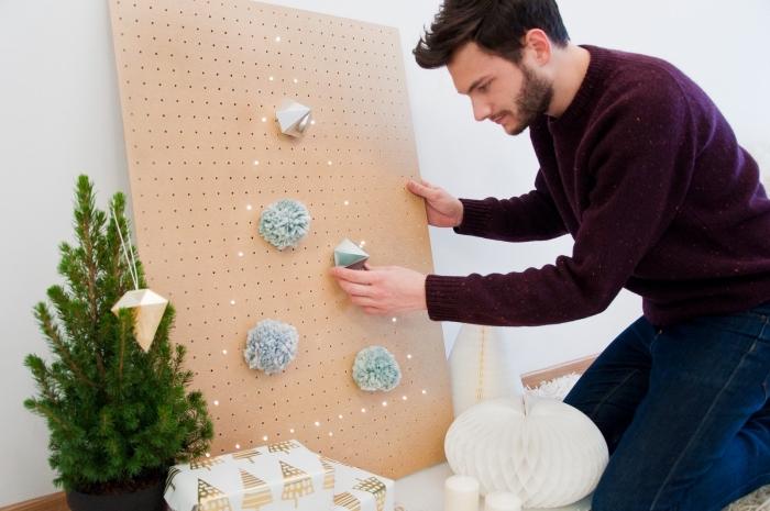 tableau peagboard avec une guirlande lumineuse en forme de sapin original, décoré de pompons en laine et des ornements géométriques