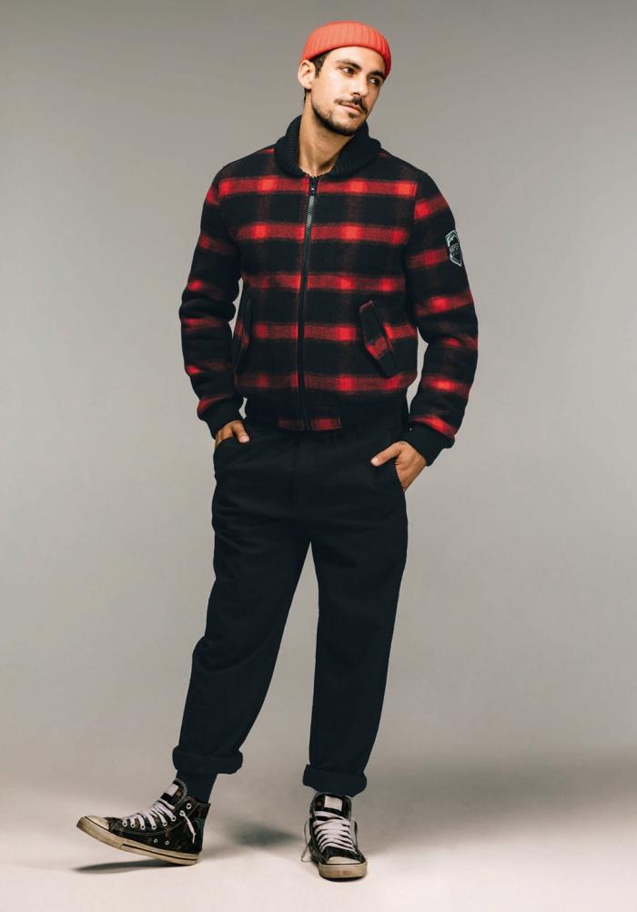 tenue d'homme style casual avec un blouson homme en laine à motifs carreaux noir et rouge combinée avec un pantalon noir, un bonnet en maille et une paire de sneakers usés