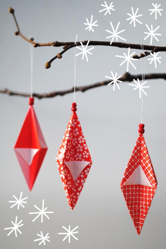 pliages origami ornements de noël géométriques en papier imprimé à motifs rouge et blanc, suspendus à une branche décorative
