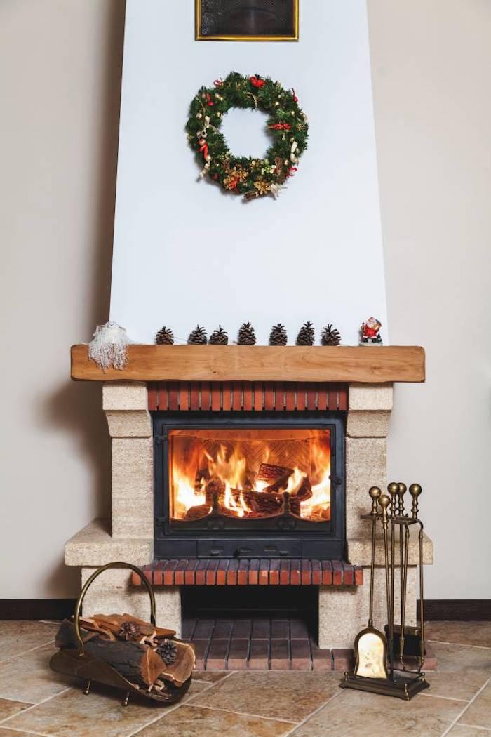 idée de cheminée traditionnelle design à foyer fermé pour maximiser la chaleur, deco couronne de noel, pommes de pin