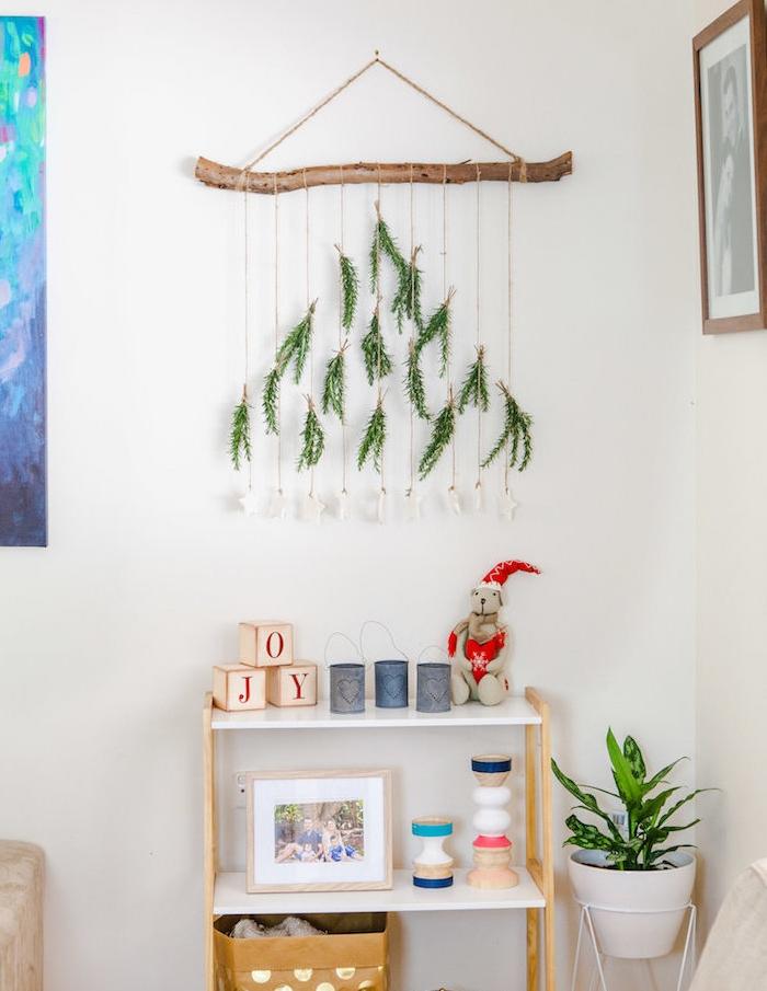 decoration murale de noel d une branche bois flotté avec des brindilles de pin suspendues, deco noel maisonscandinave