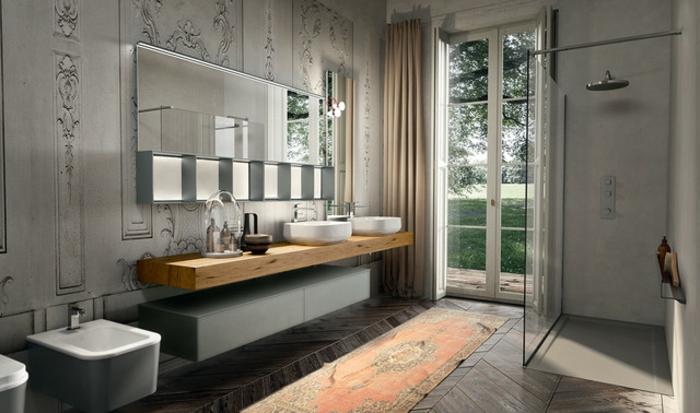 salle de bain en gris, carpette ethnique rouge, plan vasque planche de bois, porte-fenêtre, cabine de douche en béton