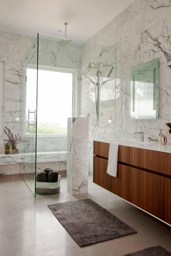 tapis gris, carrelage imitation béton, meuble vasque bois et blanc, murs marbrés, banquette suspendue sous la fenêtre