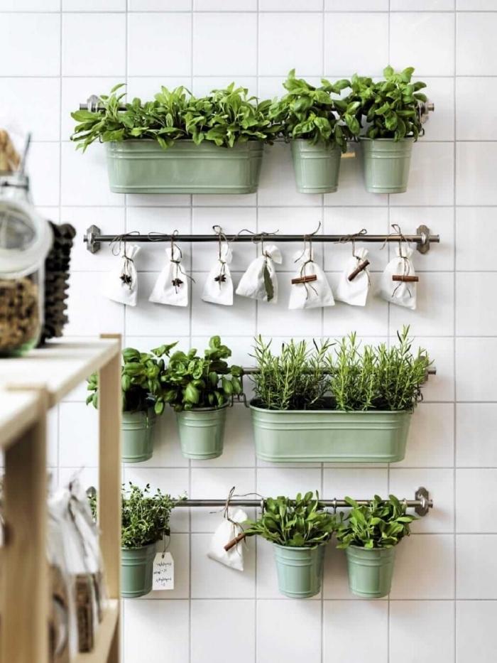 créer un petite jardin d'herbes aromatiques dans la cuisine à l'aide de jardinières en zinc couleur vert amande et des pochettes en toile suspendues sur des barres de support murales, sur le fond du mur revêtu de carrelage bmanc