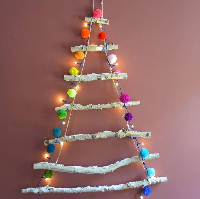 idée originale pour un sapin de noel en bois a faire soi meme, pliable et gain de place, réalisé avec des branches de bois suspendues au mur et décoré de pompons colorés et d'une guirlande led