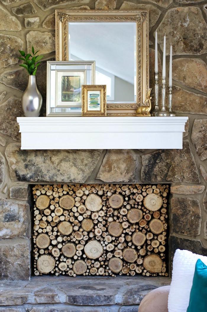 mur en pierre intérieur avec faux foyer cheminée avec buches décoratives et support blanc mural miroir et cadres photo