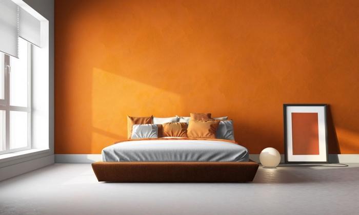 idée couleur chambre moderne en orange, peinture nuance tangerine pour une chambre à coucher, modèle de grand lit en cadre marron