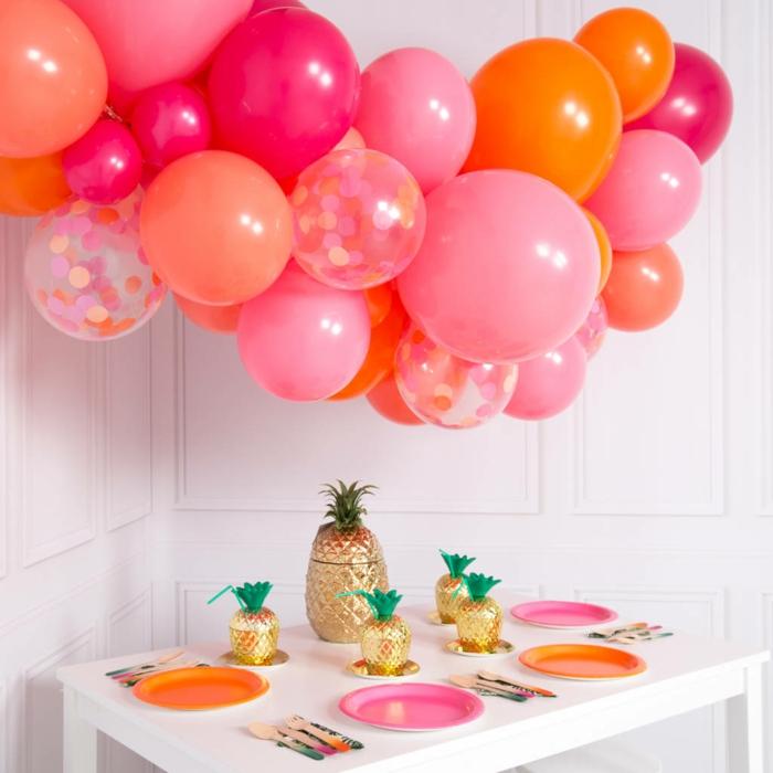 nuage de ballons en rose et orange, ananas dorés, assiettes aux couleurs des ballons, petite table blanche