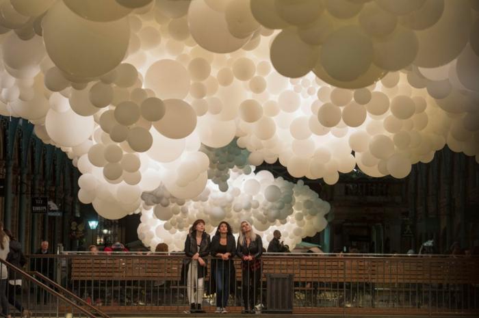 installation à Covent Garden, grandes suspensions de grappes de ballons blancs au plafond du bâtiment et spectateurs