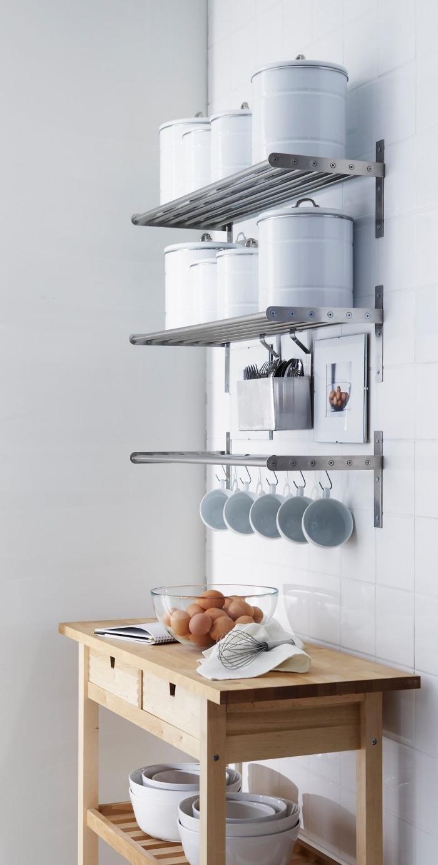 un meuble rangement cuisine mural de style industriel en acier inoxydable, des étagères murales pour casseroles et une barre porte-tasse à café avec crochets, une desserte de service en bois clair avec tiroirs et étagères