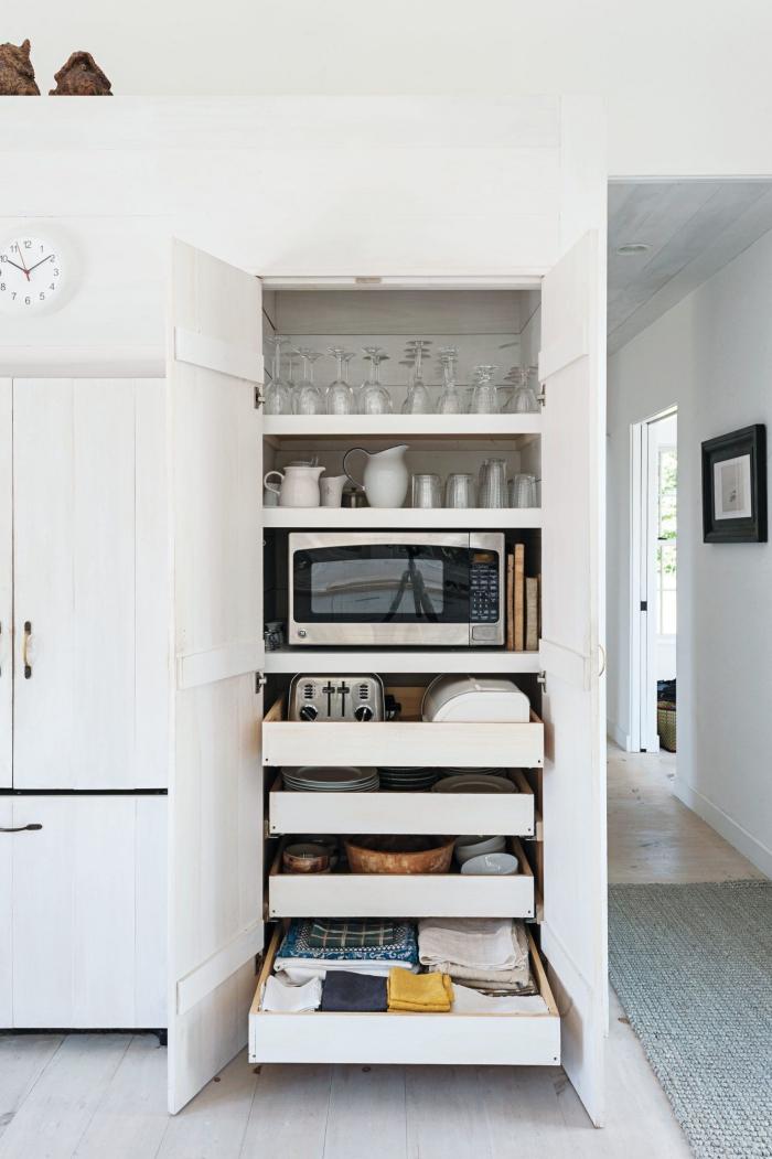 l'intérieur d'un placard avec étagères et tiroirs coulissants, qui abrite aussi le micro-ondes, amenagement placard cuisine pour mieux organiser ses ustensiles et son linge de cuisine