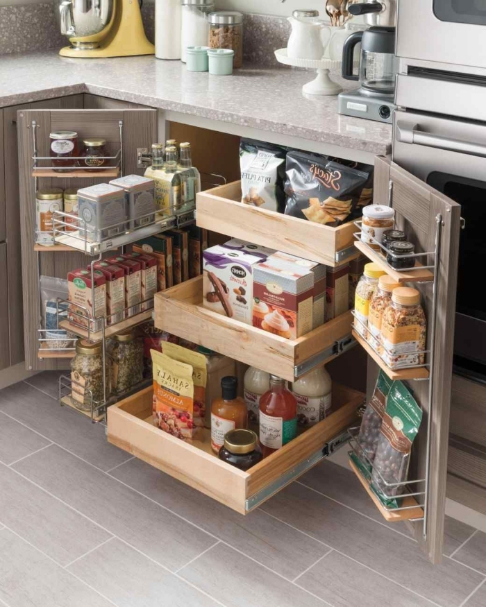 un rangement placard cuisine astucieux avec des étagères coulissantes et des organisateurs installés aux porte du placard, qui permet de gagner de la place supplémentaire